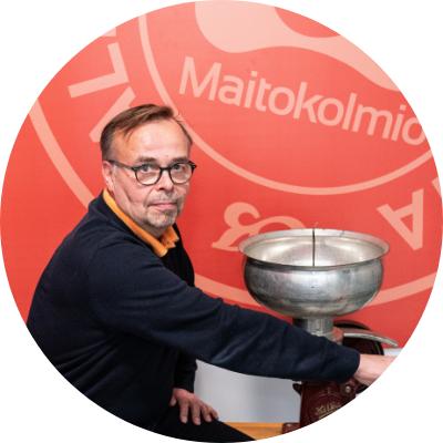 Bild på Maitokolmios vd Juha Murto--Koivosto som står bredvid gammal-dags mjölk tunna.