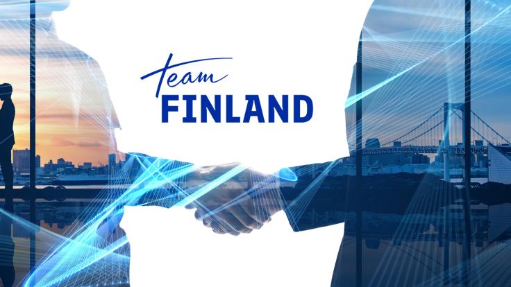 Handskakande, landskap bild på storstad och Team Finland logo