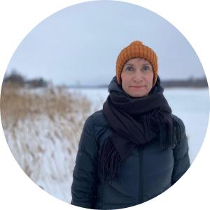 Kvinna som har vinterkläder. På backgrund finns en vintrig utsikt över sjön.
